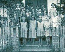 """Uczniowie na schodach przy głównym wejściu do szkoły, w chwili obecnej przybudówka tzw. """"szklarnia"""""""
