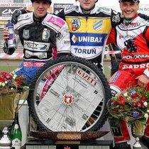 """Podium zwycięzców z pamiątkowym """"kołem"""", od lewej: Maciej Janowski (II miejsce), Darcy Ward (I miejsce) i Robert Kościecha (III miejsce)"""