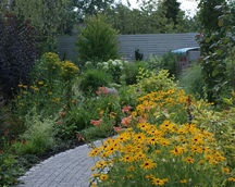 Rabaty z boku domu kipią gorącymi kolorami przez cały sezon.