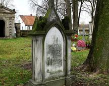 Nagrobek na przykościelnym cmentarzu. W tle kaplica grobowa.