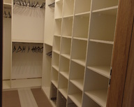 Wnętrze garderoby z białej płyty, z koszami wysuwanymi.