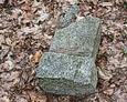 Przewrócona kamienna podstawa pod krzyż żeliwny