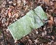 Przewrócony kamienny element nagrobny
