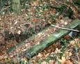 Zapadnięta i przewrócona na bok kamienna rama nagrobka