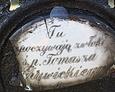 Uszkodzona porcelanowa tabliczka pamiątkowa przytwierdzona do żeliwnego krzyża