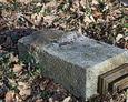 Przewrócony kamienny postument z fragmentem podstawy żeliwnego krzyża