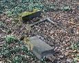 Przewrócona kamienna tablica wraz z podstawą pod krzyż
