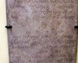 Płyta nagrobna przytwierdzona do ściany kościoła w Łebie