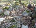 Wydobycie jednej z tablic nagrobnych ze stosu kamiennych elementów nagrobnych