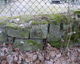 Fragmenty przedwojennych nagrobków znajdujące się w ogrodzeniu cmentarza