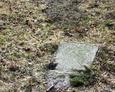 Fragment nagrobka częściowo zakopany w ziemi