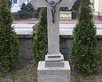 Kolejny kamienny nagrobek z krzyżem i widoczną tablicą inskrypcyjną