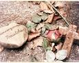 Gliniany krzyżyk z kamieniem na jednym z nagrobków (Oskowo)