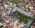 Pęknięta kamienna podstawa pod żeliwny krzyż