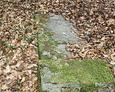 Przewrócony kamienny postument nagrobny