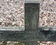 Górna część drewnianego krzyża z widoczną inskrypcją