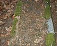 Zdewastowany nagrobek, którego brzegi wyznacza kamienna rama