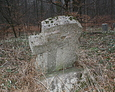 Przechylony kamienny obelisk z ,,wtopioną'' formą krzyża