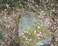 Przewrócony kamienny obelisk z niewidoczną inskrypcją