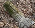 Przewrócony kamienny postument w kształcie pnia dębu