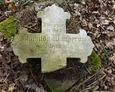 Widoczna inskrypcja na kamiennym krzyżu z dziecięcego nagrobka