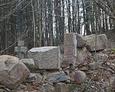 Pozostałości ściany kaplicy grobowej; w tle widoczny kamienny krzyż