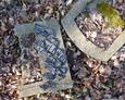 Zniszczone kamienne płyty nagrobne