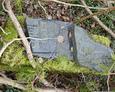 Porozbijane na drobne fragmenty tablice inskrypcyjne; jedna z nich wskazuje datę pochówku na rok 1918