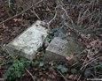 Przewrócone kamienne postumenty nagrobków
