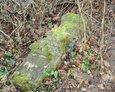 Przewrócony kamienny postument w kształcie pnia drzewa
