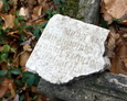 Niewielki fragment rozbitej płyty z cząstkowym fragmentem inskrypcji