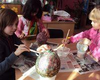 Maja i Kaja Wendland oraz Michalina Janicka wyykonują wielkanocne jaja z nici